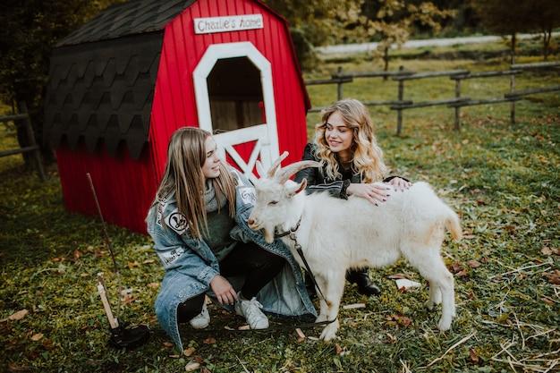 Szczęśliwe młode kobiety z kózką na wsi
