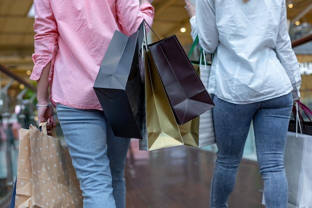 Szczęśliwe młode kobiety z torbami na zakupy cieszące się zakupami, dziewczyny bawią się swoimi zakupami. koncepcja konsumpcjonizmu i stylu życia.