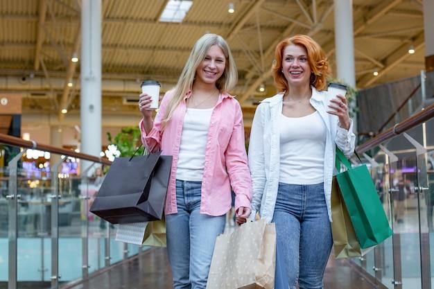 Szczęśliwe młode kobiety z torby na zakupy, ciesząc się na zakupach, dziewczyny bawią się z zakupami