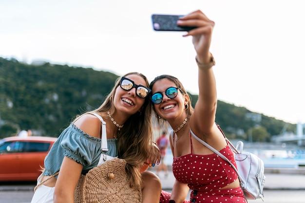 Szczęśliwe młode koleżanki w okularach przeciwsłonecznych, siedząc i biorąc selfie na telefonie komórkowym ulicy miasta city