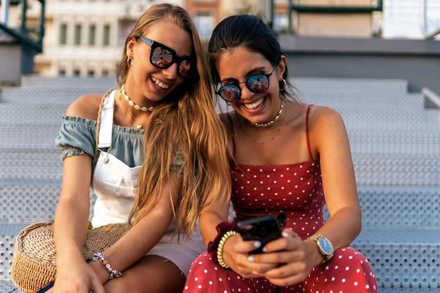 Szczęśliwe młode koleżanki w okularach przeciwsłonecznych, siedząc i przeglądając internet na telefonie komórkowym ulicy miasta