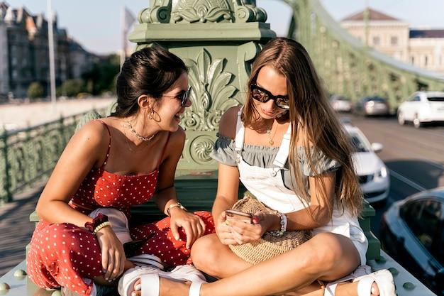 Szczęśliwe młode koleżanki w okularach przeciwsłonecznych, siedzące w pobliżu kolumny i przeglądające internet na telefonie komórkowym ulicy miasta