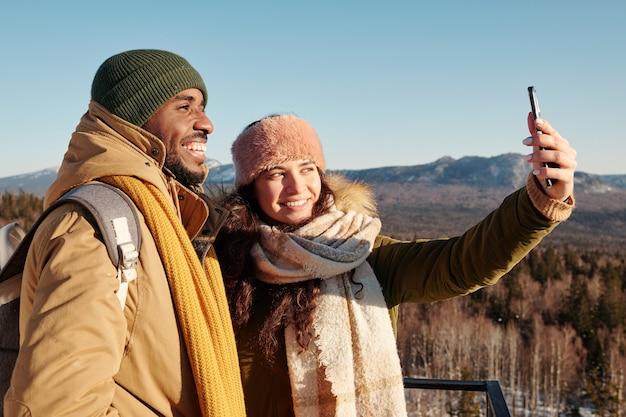 Szczęśliwe młode międzykulturowe daty w odzieży zimowej robiące selfie przed kamerą na tle błękitnego nieba nad górami pokrytymi śniegiem