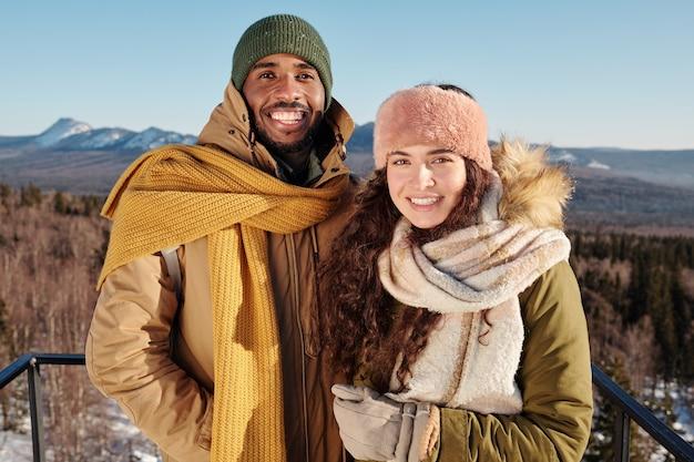 Szczęśliwe młode międzykulturowe daty w odzieży zimowej stojące na tle błękitnego nieba nad górami pokrytymi śniegiem podczas chłodu w zimowy weekend