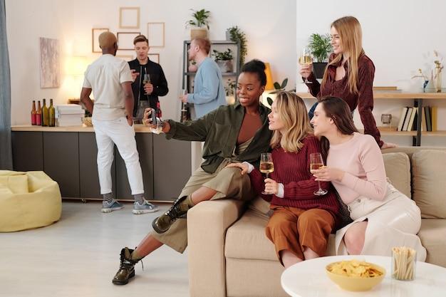 Szczęśliwe Młode Międzykulturowe Kobiety Z Kieliszkami Szampana, Patrzące Na Ciebie Z Zębami, Ciesząc Się Domową Imprezą Przeciwko Swoim Chłopakom Premium Zdjęcia