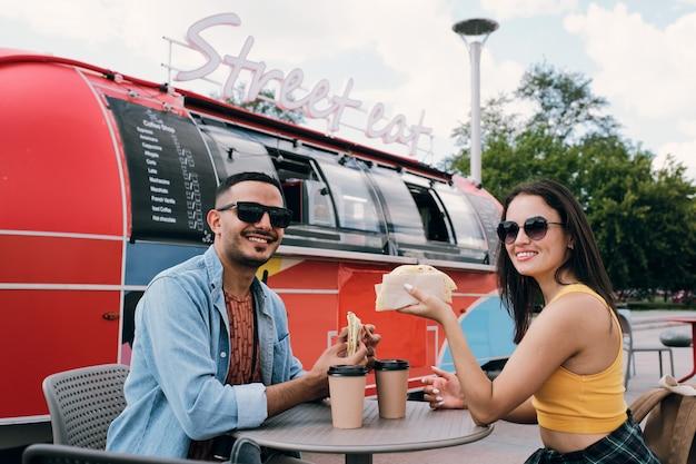 Szczęśliwe młode randki z fast foodami i napojami przy stole