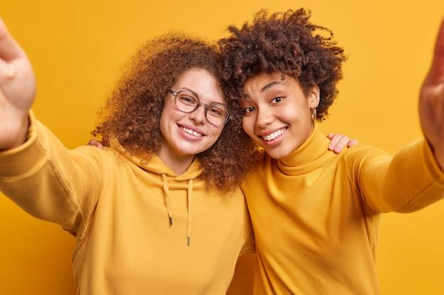 Szczęśliwe młode różnorodne kobiety mają przyjazne relacje, obejmują się i wyciągają ręce do przodu, pozują do selfie, noszą codzienne ubrania, uśmiechają się przyjemnie na białym tle nad żółtą ścianą baw się razem.