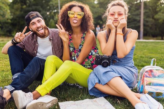Szczęśliwe młode towarzystwo przyjaciół siedzących w parku, mężczyzny i kobiet, którzy razem bawią się, podróżują z aparatem, zabawne emocjonalne