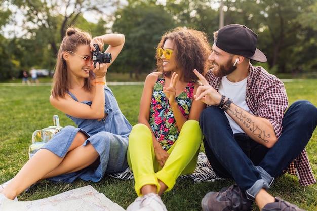 Szczęśliwe młode towarzystwo przyjaciół siedzących w parku, mężczyzny i kobiet, wspólnej zabawy, podróżowania z aparatem, robienia zdjęć