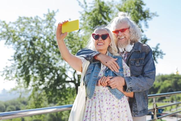 Szczęśliwe momenty. radosna starsza kobieta stojąca z mężem podczas robienia selfie ze smartfonem
