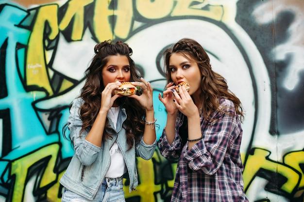 Szczęśliwe nastolatki jedzące lunch na ulicy z fryzurami.
