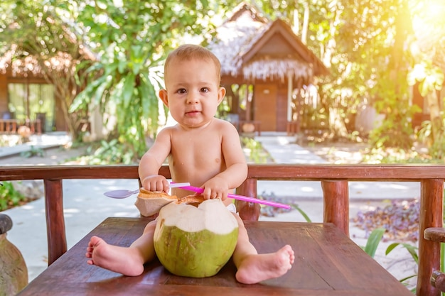 Szczęśliwe niemowlę na tropikalnych wakacjach je i pije zielony młody kokos siedzi na ziemi