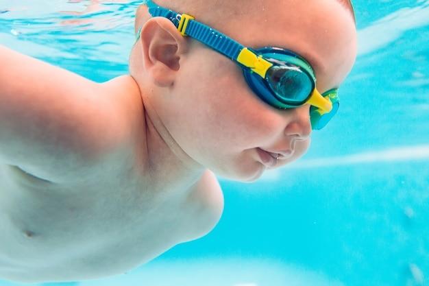 Szczęśliwe niemowlę uczy się pływać.
