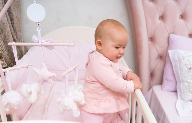 Szczęśliwe niemowlę w różowej scenie łóżeczka i sypialni z wiszącą karuzelą.