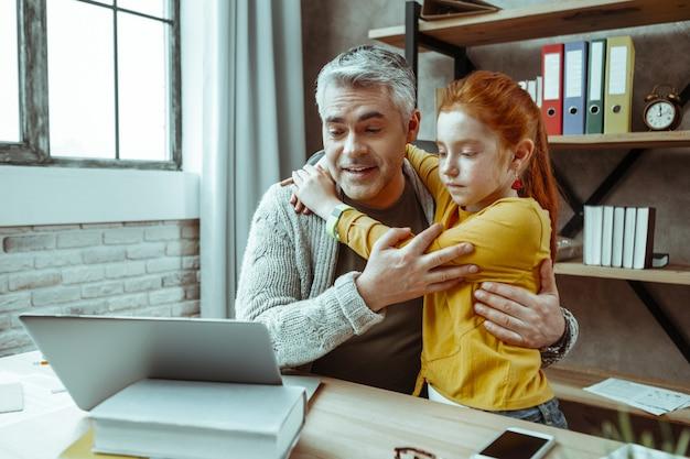 Szczęśliwe ojcostwo. pozytywny, wesoły mężczyzna patrzący na ekran laptopa, przytulając swoją córkę