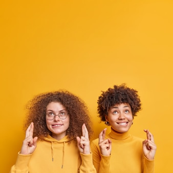 Szczęśliwe optymistyczne kobiety z kręconymi włosami krzyżują palce na szczęście, czekają na szczęście, modlą się i patrzą w górę, ubrane swobodnie błagają o spełnienie życzeń, odizolowane nad żywą żółtą ścianą z pustą przestrzenią