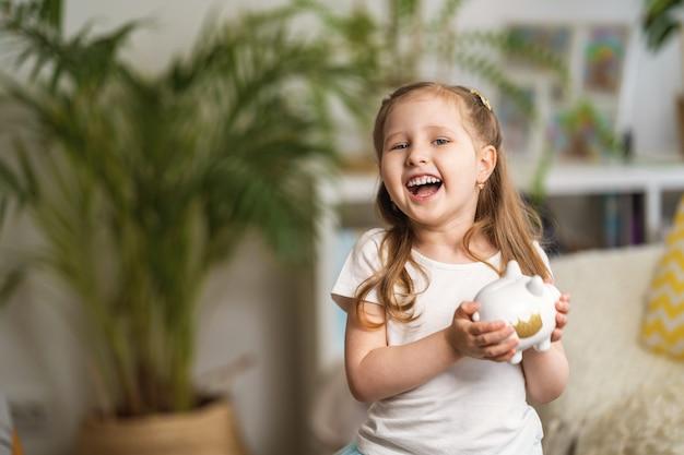 Szczęśliwe oszczędności. mała roześmiana dziewczyna z skarbonką, w domu.