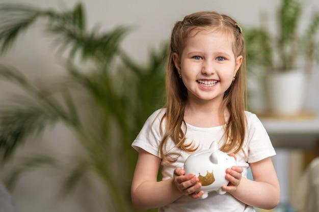 Szczęśliwe oszczędności. troszkę śliczna dziewczyna z prosiątko bankiem w domu