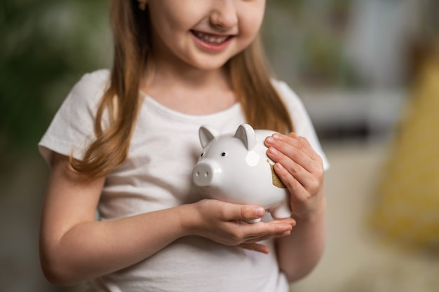 Szczęśliwe oszczędności. zakończenie, mała śliczna dziewczyna z białą prosiątko bankiem w jej rękach