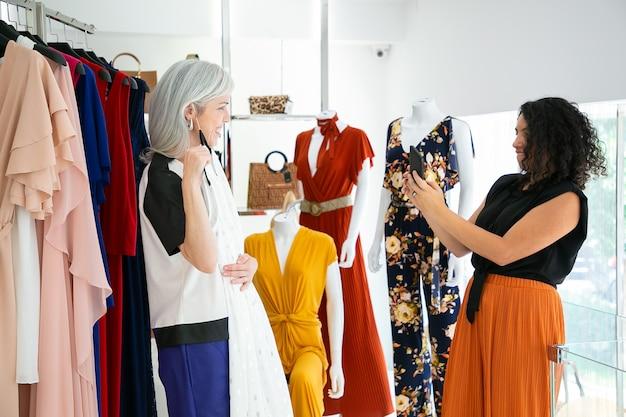 Szczęśliwe panie cieszą się razem zakupy w sklepie z modą, wybierając sukienkę i robienie zdjęć na smartfonie. widok z boku. koncepcja konsumpcjonizmu lub zakupów