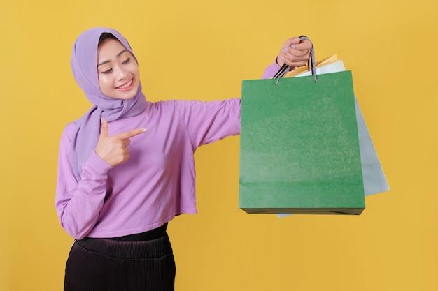Szczęśliwe piękne azjatyckie zakupoholiczki trzymając torby na zakupy