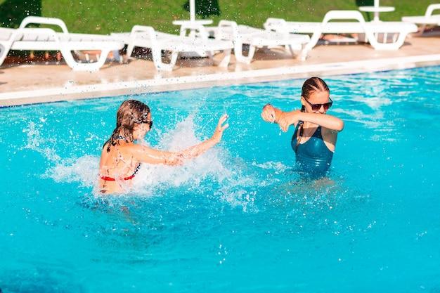 Szczęśliwe piękne dziewczyny bawiące się na basenie w ośrodku?