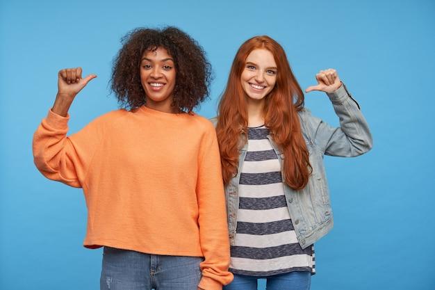 Szczęśliwe piękne panie są w dobrym nastroju, pozują na niebieskiej ścianie i uśmiechają się przyjemnie, trzymając ręce uniesione i wskazujące na siebie kciukami