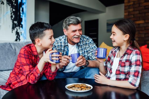 Szczęśliwe pokolenia. radosny uśmiechnięty starszy mężczyzna pije herbatę z ciastkiem, ciesząc się czasem ze swoimi wnukami.