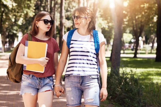 Szczęśliwe pozytywne atrakcyjne studentki lesbijki trzymają się za ręce, noszą plecaki, prowadzą przyjazne rozmowy, mówią o życiu uniwersyteckim, cieszą się słońcem, ubierają się swobodnie. powrót do koncepcji szkoły.