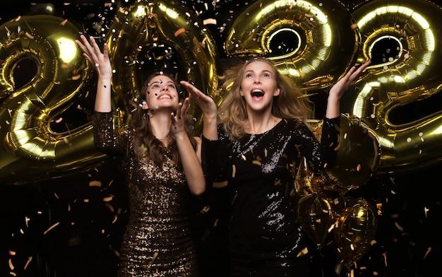 Szczęśliwe przepiękne dziewczyny w stylowych seksownych sukienkach imprezowych trzymających złote balony 2022, bawiące się na przyjęciu świątecznym lub sylwestrowym.