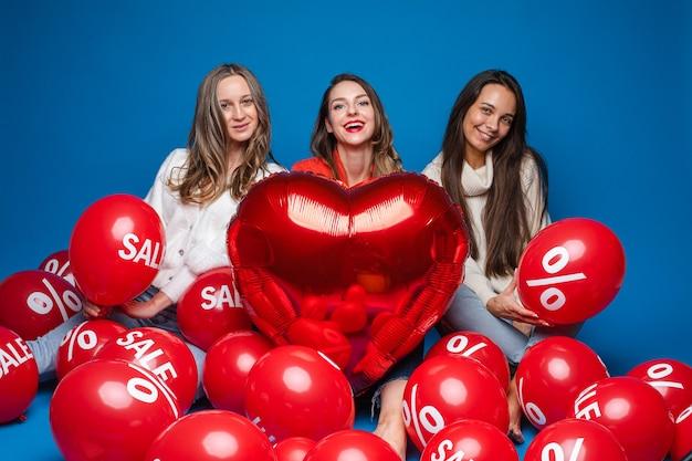 Szczęśliwe przyjaciółki pozujące z balonem w kształcie czerwonego serca i kulkami powietrznymi z napisem procentu i sprzedaży na niebieskim tle