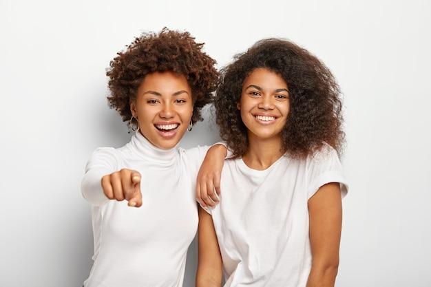 Szczęśliwe, przyjazne dwie tysiącletnie dziewczyny mają zadowolone twarze, stoją obok siebie, wskazują na odległość