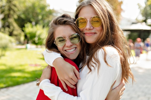 Szczęśliwe przyjazne dziewczyny przytulające się z prawdziwym uśmiechem i bawiące się na świeżym powietrzu. portret dwóch podekscytowanych pań wyrażających pozytywne emocje podczas spacerów.