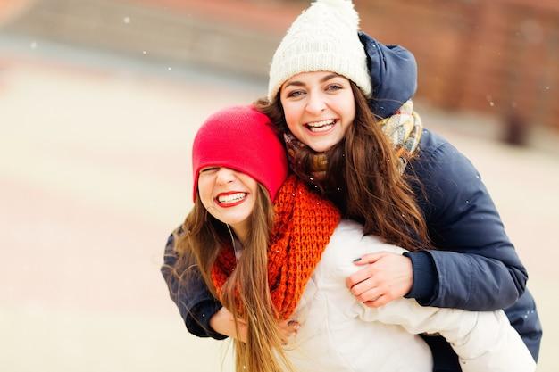 Szczęśliwe, radosne, pozytywne chwile dwóch stylowych dziewczyn przytulających się na ulicy w mieście.