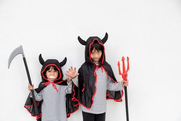 Szczęśliwe rodzeństwo dziewczyny na imprezie halloween. dzieci noszące kostiumy halloweens. koncepcja dzieci gotowe na imprezę.