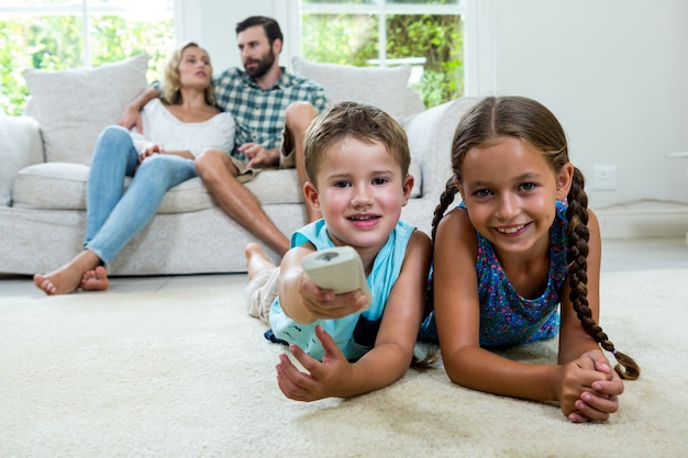 Szczęśliwe rodzeństwo ogląda telewizję przeciw rodzicom relaksuje w domu