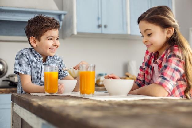 Szczęśliwe rodzeństwo. przystojny, wesoły mały ciemnowłosy chłopiec patrząc na swoją siostrę i uśmiechnięty i mają zdrowe śniadanie