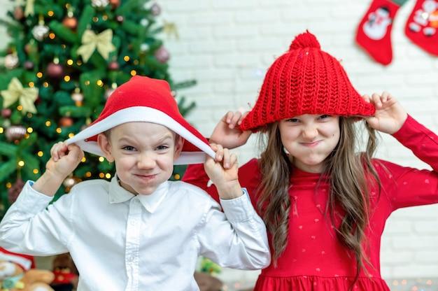 Szczęśliwe rodzeństwo w świątecznych strojach na podłodze w pobliżu choinki w domu. szczęśliwy pomysł rodzinny
