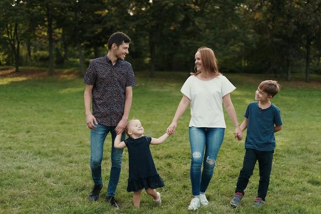 Szczęśliwe rodzinne mienie ręki podczas gdy chodzący parka