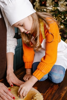 Szczęśliwe rodzinne przygotowanie świątecznych posiłków w domu. matka i córka przygotowują świąteczne ciasteczka.
