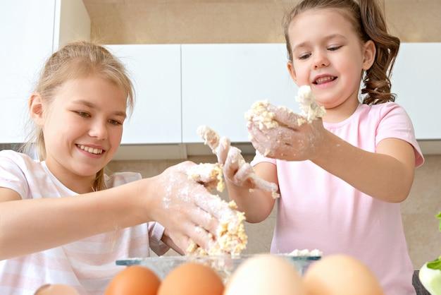 Szczęśliwe rodzinne śmieszne dzieci przygotowują ciasto, piec ciastka w kuchni. siostry bawią się razem śmiejąc się