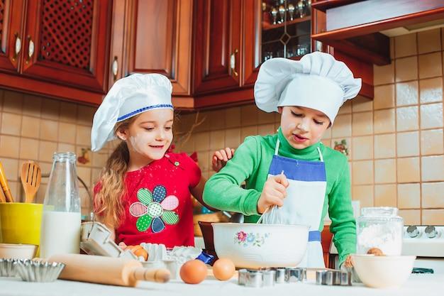 Szczęśliwe rodzinne śmieszne dzieci przygotowują ciasto, piec ciastka w kuchni