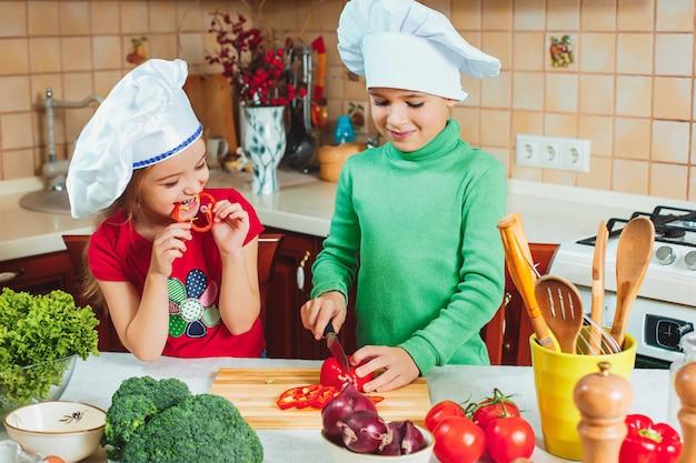 Szczęśliwe rodzinne śmieszne dzieci przygotowują sałatkę ze świeżych warzyw w kuchni