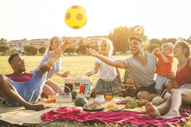 Szczęśliwe rodziny robi piknik w parku miejskim. młodzi rodzice bawią się ze swoimi dziećmi latem, jedząc, pijąc i śmiejąc się razem