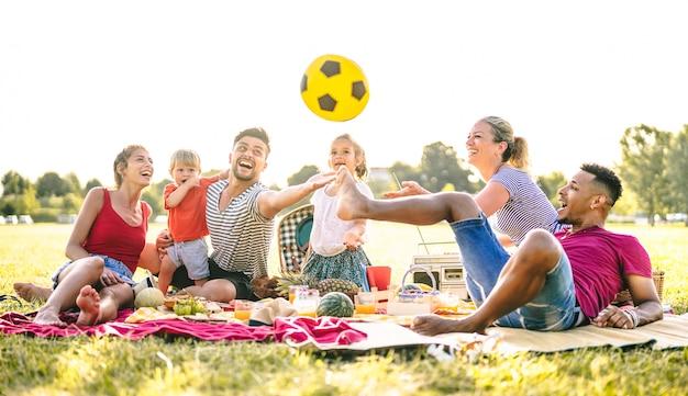Szczęśliwe rodziny wielorasowe bawiące się z uroczymi dziećmi na piknikowym przyjęciu w ogrodzie