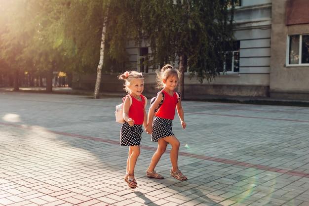 Szczęśliwe siostry dziewczyny są ubranym plecaki i biegają. dzieci uczniowie bawią się w pobliżu szkoły. edukacja