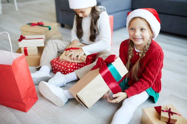 Szczęśliwe siostry rozpakowujące świąteczne prezenty lub prezenty
