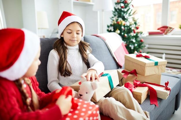 Szczęśliwe siostry siedzące na kanapie i rozpakowujące świąteczne prezenty