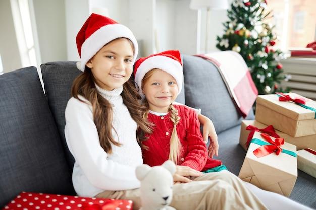 Szczęśliwe siostry siedzi na kanapie z prezentami świątecznymi