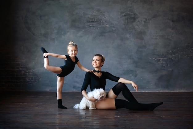 Szczęśliwe słodkie gimnastyczki mama i córka z psem białego teriera